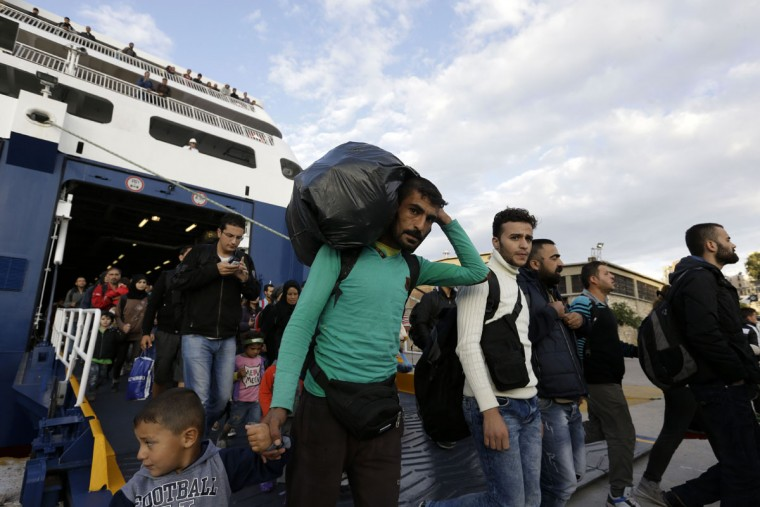 A man carries his belongings as other migrants and refugees arrive on a ferry from the Greek island of Lesbos at the Athens' port of Piraeus, Wednesday, Sept. 30, 2015. The Greek ferry Blue Star Patmos is part of special ferry service for refugees and migrants that carries 1,800 paying passengers. The International Organization for Migration says a record number of people have crossed the Mediterranean into Europe this year, now topping a half a million as some 388,000 have entered via Greece. (AP Photo/Thanassis Stavrakis)