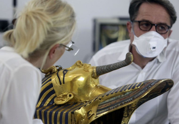 German restorers Christian Eckmann, right, and Katja Broschat examine the famed golden mask of King Tutankhamun as an Egyptian-German team begins restoration work over a year after the beard was accidentally broken off and hastily glued back with epoxy, at the Egyptian Museum in Cairo, Egypt, Tuesday, Oct. 20, 2015. The 3,300-year-old burial pharaonic mask was discovered in Tutankhamun's tomb along with other artifacts by British archeologists in 1922, sparking worldwide interest in archaeology and ancient Egypt. (AP Photo/Amr Nabil)