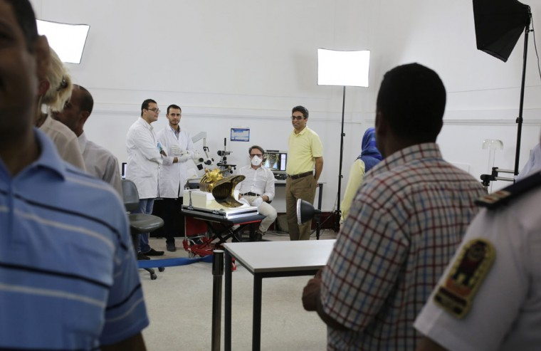 Egyptian officials and security guards watch as an Egyptian-German team led by German restorer Christian Eckmann (fourth from right) begin restoration of the famed golden mask of King Tutankhamun over a year after the beard was accidentally broken off and hastily glued back with epoxy, at the Egyptian Museum in Cairo, Egypt, Tuesday, Oct. 20, 2015. The 3,300-year-old burial pharaonic mask was discovered in Tutankhamun's tomb along with other artifacts by British archeologists in 1922, sparking worldwide interest in archaeology and ancient Egypt. (AP Photo/Amr Nabil)
