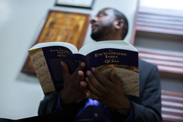 Rashad Abdul-Rahman holds a book at the Atlanta Masjid of Al Islam mosque, Sunday, Aug. 30, 2015, in Atlanta. Members of the mosque gathered to celebrate a group of pilgrims who will make the annual Hajj pilgrimage to the holy city of Mecca. (AP Photo/Branden Camp)