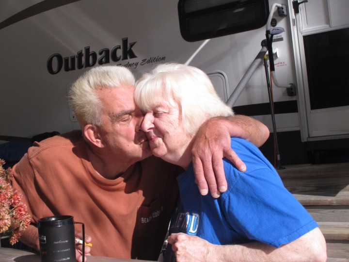In this Oct. 21, 2015, photo, Bob Collis, left, kisses his wife, Katherine, right, in front of their trailer in Berkeley Township, N.J. They have been unable to return to their home in Toms River, N.J., since Superstorm Sandy damaged it three years ago. (AP Photo/Wayne Parry)