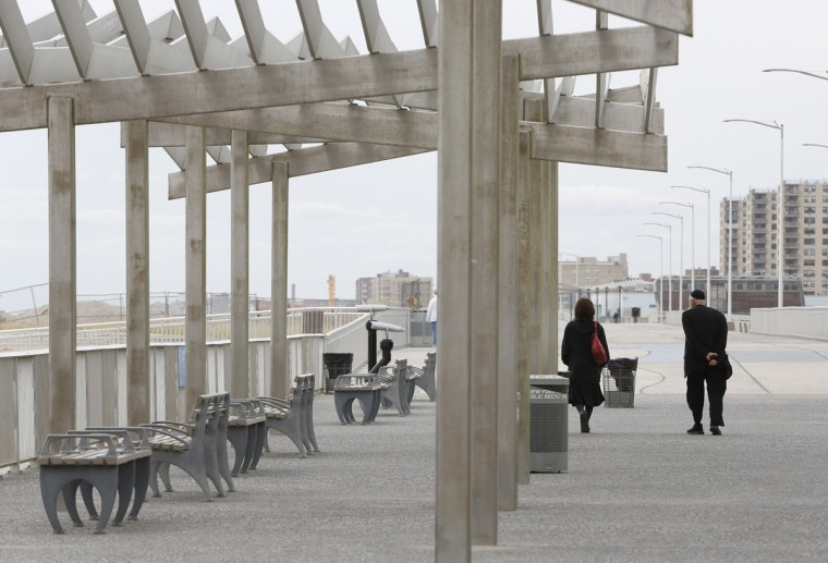 A couple strolls on a newly constructed concrete portion of the Rockaway Beach boardwalk near Beach 88th Street before the third anniversary of Superstorm Sandy, Tuesday, Oct. 27, 2015, in New York. Work involving the New York City Economic Development Corporation and the U.S. Army Corps of Engineers is ongoing to provide more long-term protection for the environmentally sensitive area. (AP Photo/Kathy Willens)