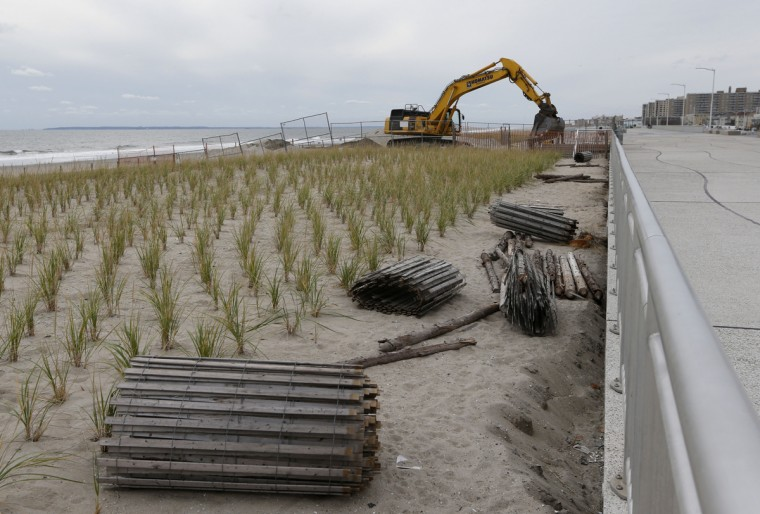 An excavator moves sand into place as work continues rebuilding the heavily damaged Rockaway Beach boardwalk before the third anniversary of Superstorm Sandy in New York, Tuesday, Oct. 27, 2015. A new concrete section of the boardwalk is visible, right, with freshly planted sea grasses, left, to reduce erosion from the ocean. Since the devastating storm, more than $140 million has been invested to repair and restore the beach. The New York City Department of Parks and Recreation estimates more than 4 million people visited Rockaway Beach last summer. (AP Photo/Kathy Willens)