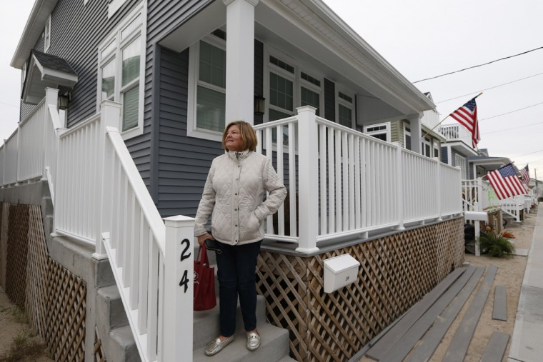 Maureen Farrell stands on the stoop of her new home in the Breezy Point neighborhood, rebuilt on the site of her house that burned to the ground from a massive fire from Superstorm Sandy in New York, Tuesday, Oct. 27, 2015. Displaced since the storm, Farrell just moved back into her house in July 7. (AP Photo/Kathy Willens)