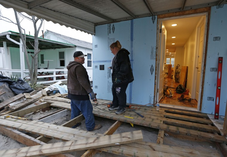 "Habitat for Humanity employees Reynaldo and Anna Acosta hurry to complete the deck of a heavily damaged one-story bungalow owned by a 91-year-old resident in Breezy Point, before the third anniversary of Superstorm Sandy in New York, Tuesday, Oct. 27, 2015. The couple has worked exclusively on rebuilding homes damaged by the storm for nearly the entire three years, initially as volunteers and now as Habitat employees. ""No matter how much work we do,"" says Anna Acosta, ""there's always more to do."" According to Breezy Point Cooperative general manager Arthur Lighthall, 220 Breezy Point homes were completely destroyed by flooding during Sandy. (AP Photo/Kathy Willens)"