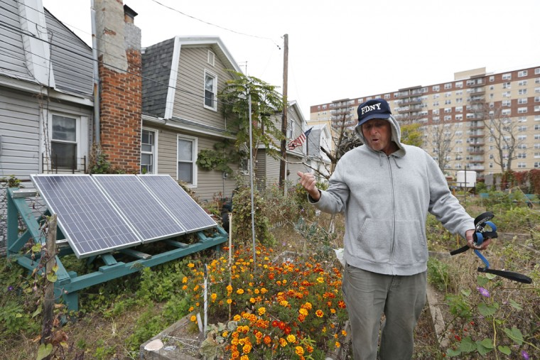 "Retiree Buddy Sammis gestures toward solar panels he and his neighbors used to change their cell phones three years ago after portions of the Rockaway Beach boardwalk washed onto his street severing power lines, as he walks through a neighborhood-run community garden in the Rockaways Tuesday, Oct. 27, 2015, in New York before the third anniversary of Superstorm Sandy. Sammis a longtime surfer, said, ""I miss the (old) boardwalk. It was iconic. It was the longest boardwalk in the world, when it went all the way to 126th Street. Now it's all cement. That's not going to stop anything. If the ocean wants to take the concrete away, it'll happen."" (AP Photo/Kathy Willens)"