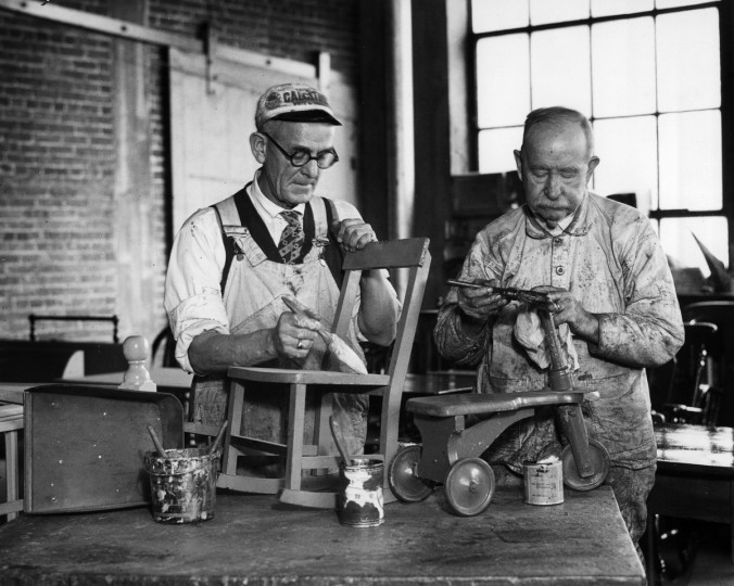 1933 - J. Benjamin Ayres, left, and H.G. Murray, right, are busy repairing toys at the Good Will Industries shop in Baltimore in this scene. (A. Aubrey Bodine/Baltimore Sun)