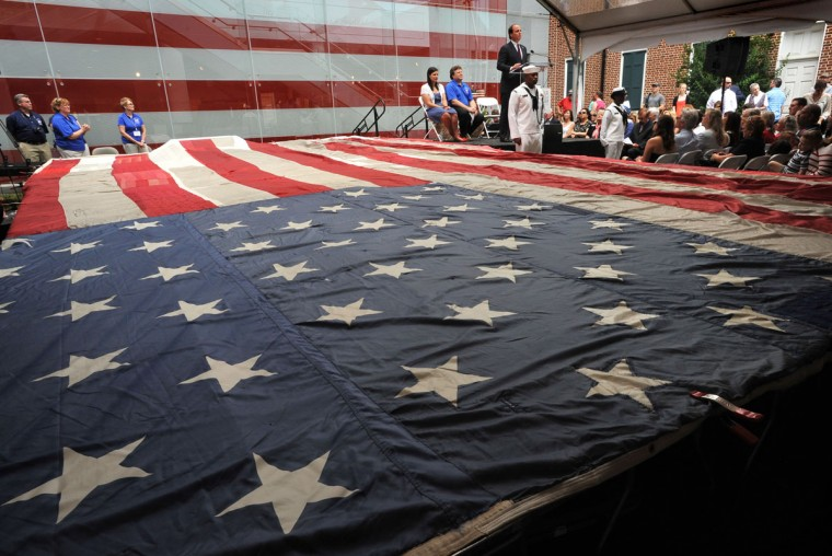 A patch with three threads from the original Star-Spangled Banner was stitched onto the National 9/11 Flag on June 14, 2012 at a ceremony at the Flag House. Dozens of invited guests and children in attendance participated in adding a stitch to the patch on the flag that flew in N.Y. at 90 West Street after 9/11. (Baltimore Sun photo by Amy Davis)