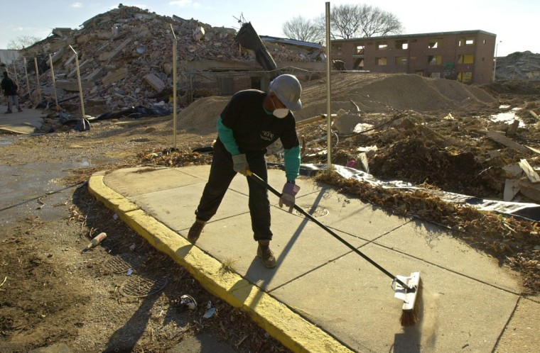 Bruce Davis sweeps debris from the sidewalk following demolition of the Flag House Courts high rises on Feb. 10, 2001. (Baltimore Sun photo by Doug Kapustin)