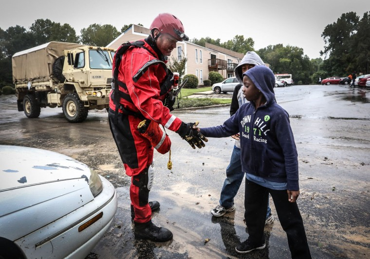 Zahid and Davon Richardson are greeted by a rescue team in the Shandon Crossing apartment complex on Oct. 5, 2015 in Columbia, S.C. Rescue crews from across the country worked to help those in need after rain and flood water ravaged the area. (Matt Walsh/The State/TNS)