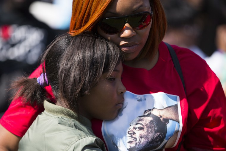 Margaret Holland, of Baltimore, Md., right, hugs her nine year-old daughter Jaylah Sabb during a rally to mark the 20th anniversary of the Million Man March, on Capitol Hill, on Saturday, Oct. 10, 2015, in Washington. (AP Photo/Evan Vucci)