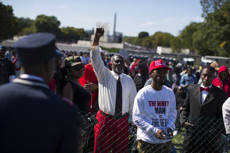 People look on as Minister Louis Farrakhan speaks during a rally to mark the 20th anniversary of the Million Man March, on Capitol Hill, on Saturday, Oct. 10, 2015, in Washington. (AP Photo/Evan Vucci)