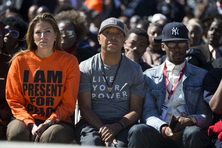 Artist and entrepreneur Russell Simmons, center, looks on as Minister Louis Farrakhan speaks during a rally to mark the 20th anniversary of the Million Man March, on Capitol Hill, on Saturday, Oct. 10, 2015, in Washington. (AP Photo/Evan Vucci)