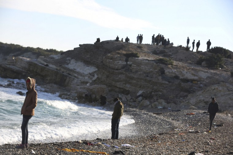 Migrants and refugees watch the rough sea as they wait to cross to the Greek island of Chios, near Cesme, Turkey, Sunday, Nov. 1, 2015. Greek authorities recovered more bodies on the Greek islands of Samos and Lesbos Sunday as thousands continue to cross the Aegean Sea from the nearby coast of Turkey despite worsening weather. (AP Photo/Emre Tazegul)