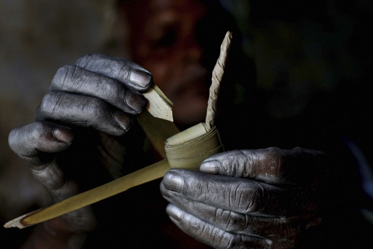 "An Indian village man folds palm leaves as he makes firecrackers with bare hands at his workshop at Bhingharpur village, outskirts of Bhubaneswar, Orissa state, India, Monday, Nov. 2, 2015. Fire crackers are in high demand in India during the upcoming festival of lights, ""Diwali"". (AP Photo/Biswaranjan Rout)"