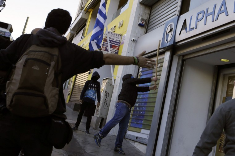 A youth tries to break a sign on a bank during a protest in Athens, Monday, Nov. 2, 2015. About 5,000 people took part in a demonstration demanding more funds for schools to address the deficiencies and gaps in education. (AP Photo/Thanassis Stavrakis)