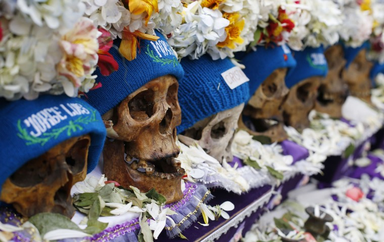 "Human skulls or ""natitas"" crowned with flowers and surrounded by offerings of coca leaves, flower petals and cigarettes, are displayed outside the Cementerio General chapel, during the Natitas Festival, in La Paz, Bolivia, Sunday, Nov. 8, 2015. Although some natitas have been handed down through generations, many are from unnamed, abandoned graves. The are cared for and decorated by faithful who use them as amulets believing they serve as protection. The tradition marks the end of the Catholic All Saints holiday, but is not recognized by the Catholic church. (AP Photo/Juan Karita)"