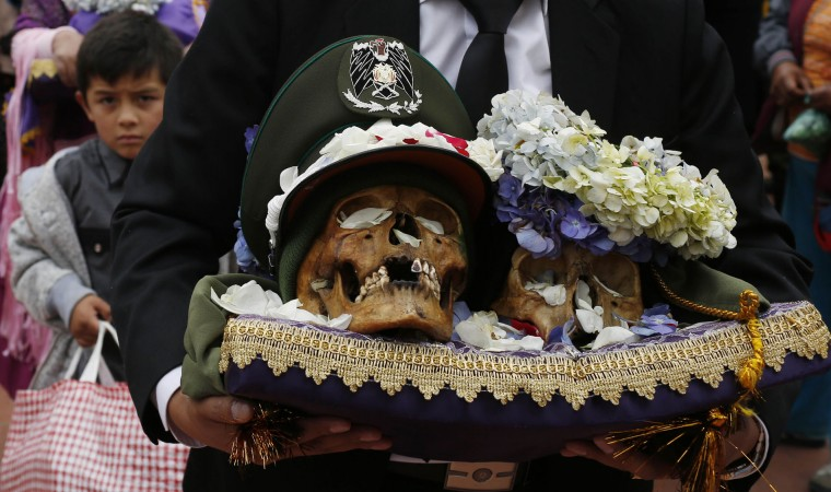 "A man carries decorated human skulls or ""natitas"" outside the Cementerio General chapel, during the Natitas Festival celebrations, in La Paz, Bolivia, Sunday, Nov. 8, 2015. Although some natitas have been handed down through generations, many are from unnamed, abandoned graves that are cared for and decorated by faithful who use them as amulets believing they serve as protection. The tradition marks the end of the Catholic All Saints holiday, but is not recognized by the Catholic church. (AP Photo/Juan Karita)"