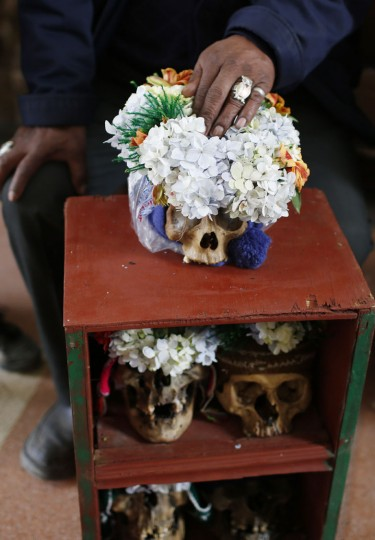 "A man holds decorated human skulls or ""natitas"" as he waits to be greeted by the priest inside the Cementerio General chapel, during the Natitas Festival celebrations, in La Paz, Bolivia, Sunday, Nov. 8, 2015. Although some natitas have been handed down through generations, many are from unnamed, abandoned graves that are cared for and decorated by faithful who use them as amulets believing they serve as protection. The tradition marks the end of the Catholic All Saints holiday, but is not recognized by the Catholic church. (AP Photo/Juan Karita)"