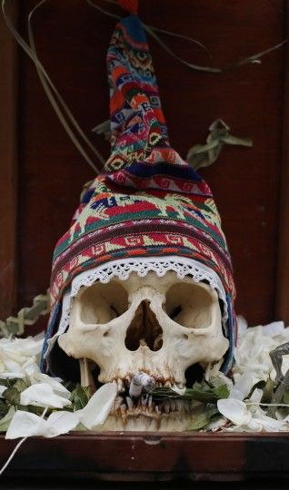 "A human skull or ""natitas"" surrounded by offerings of coca leaves, flower petals and cigarettes, is displayed outside the Cementerio General chapel, during the Natitas Festival, in La Paz, Bolivia, Sunday, Nov. 8, 2015. Although some natitas have been handed down through generations, many are from unnamed, abandoned graves that are cared for and decorated by faithful who use them as amulets believing they serve as protection. The tradition marks the end of the Catholic All Saints holiday, but is not recognized by the Catholic church. (AP Photo/Juan Karita)"