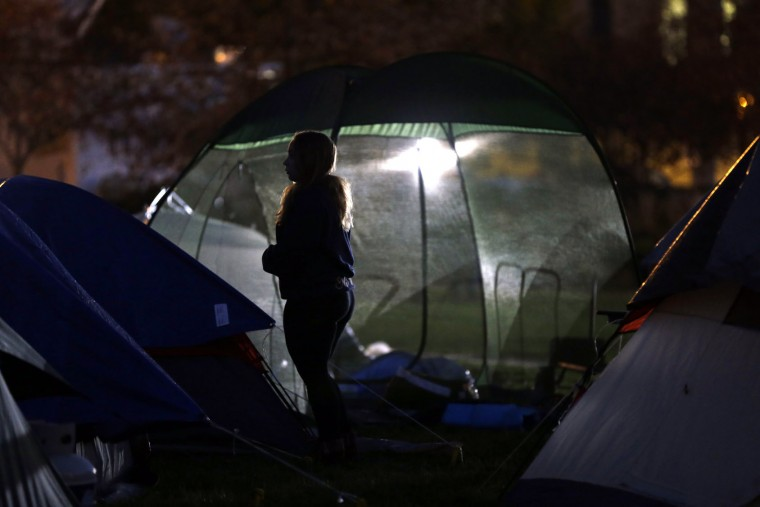A student protester stands between tents set up in an encampment as night falls Monday, Nov. 9, 2015, on the University of Missouri campus in Columbia, Mo. The president of the University of Missouri System and the head of its flagship campus resigned Monday with the football team and others on campus in open revolt over what they saw as indifference to racial tensions at the school. (AP Photo/Jeff Roberson)
