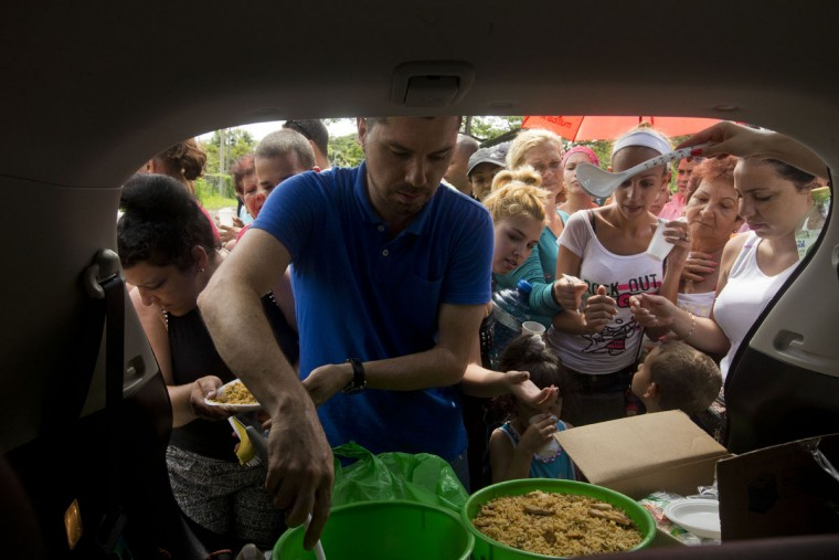 A Costa Rican man give a food to Cuban migrants at the Costa Rican border with Nicaragua, in Penas Blancas, Monday, Nov. 16, 2015. More than 1 thousand Cuban migrants heading north to the United States tried to cross the border from Costa Rica into Nicaragua, causing tensions to soar between the neighbors as Nicaraguan security forces sought to turn them back. Following the thaw in relations between Washington and Havana, some Cubans have been making their way to Central America in hopes of then heading through Mexico and into the United States. (AP Photo/Esteban Felix)