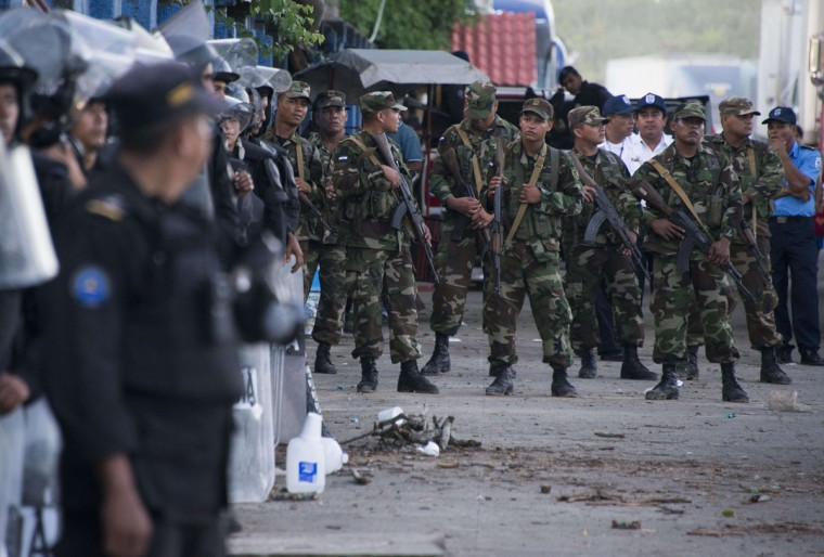 Nicaraguan soldiers and policemen stand guard in Penas Blancas, Guanacaste, Costa Rica, in the border with Nicaragua on November 16, 2015. A surge of some 2,000 Cuban migrants trying to cross Central America to reach the United States triggered a diplomatic spat between Costa Rica and Nicaragua Monday, plunging tense relations between the two countries to a new low. (AFP Photo/Ezequiel Becerra)