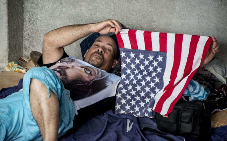 A Cuban from a group of 150 resting in a shelter in the town of La Cru , Guanacaste, Costa Rica, near the border with Nicaragua holds a U.S. flag, on November 17, 2015. A surge of some 2,000 Cuban migrants trying to cross Central America to reach the United States triggered a diplomatic spat between Costa Rica and Nicaragua Monday, plunging tense relations between the two countries to a new low. (AFP Photo/Ezequiel Becerra)
