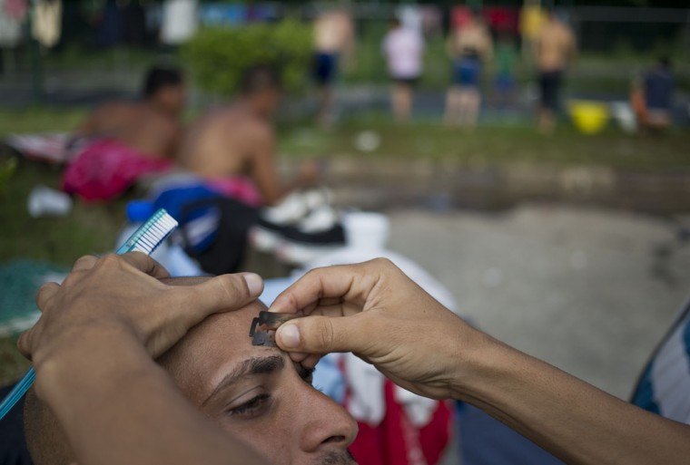 "A Cuban migrant uses a a razor blade to style the eyebrow of a fellow migrant outside the immigration office in PeÒas Blancas, Costa Rica, Tuesday, Nov. 17, 2015. Costa Rican Foreign Minister Manuel Gonzalez said in a radio interview Tuesday that there are nearly 2,000 people currently at the border being blocked by Nicaraguan soldiers from entering the country. He proposed the creation of a ""humanitarian corridor"" for Cubans transiting Central America. (AP Photo/Esteban Felix)"