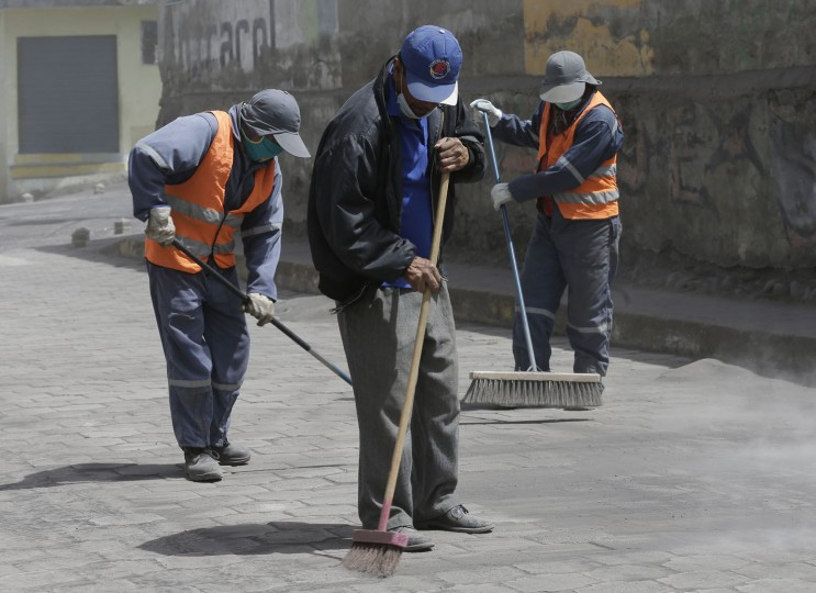 City workers, wearing masks as protection from the steady rain of volcanic ash spewed by the nearby Tungurahua volcano, sweep ash from the stone streets, in Quero, Ecuador, Thursday, Nov. 19, 2015. Volcano monitors say about a dozen farming villages have been dusted with ash due to bursts from Ecuador''s Tungurahua volcano. Thursday''s report comes a day after authorities imposed new precautionary measures around the volcano, which has been increasingly restive. (AP Photo/Dolores Ochoa)