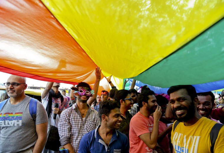 Members and supporters of lesbian, gay, bisexual and transgender community, some wearing masks participate in 'Pride March' rally in Bangalore, India, Sunday, Nov. 22, 2015. Gay rights supporters waved flags and danced past traffic during the march to celebrate gay pride and to push for the repeal of a colonial-era law that makes homosexuality a crime. (AP Photo/Aijaz Rahi)
