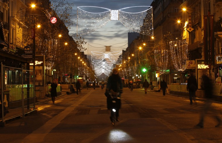 A cyclist makes her way along a pedestrian street lit with Christmas decorations in central Brussels at dusk on Monday, Nov. 23, 2015. Three days of the highest terror alert and unprecedented measures that have closed down the city's subways, schools and main stores, has created a very different atmosphere as the Belgian capital tries to avoid attacks similar to the ones that caused devastating carnage in Paris. (AP Photo/Alastair Grant)