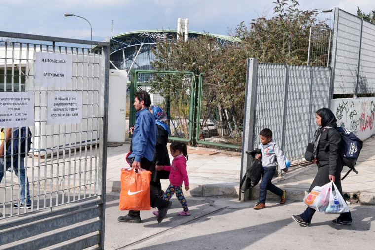ATHENS, GREECE - OCTOBER 7: Newly arrived immigrants enter Galatsi Olympic Hall on October 7, 2015 in Athens, Greece. Greek authorities reopened the Galatsi Olympic Hall in a bid to accommodate some of the immigrants who have arrived in the country recently. About 800 people, mostly from Syria and Afghanistan, were bused to the stadium from Athen's central Victoria Square. (Photo by Milos Bicanski/Getty Images)