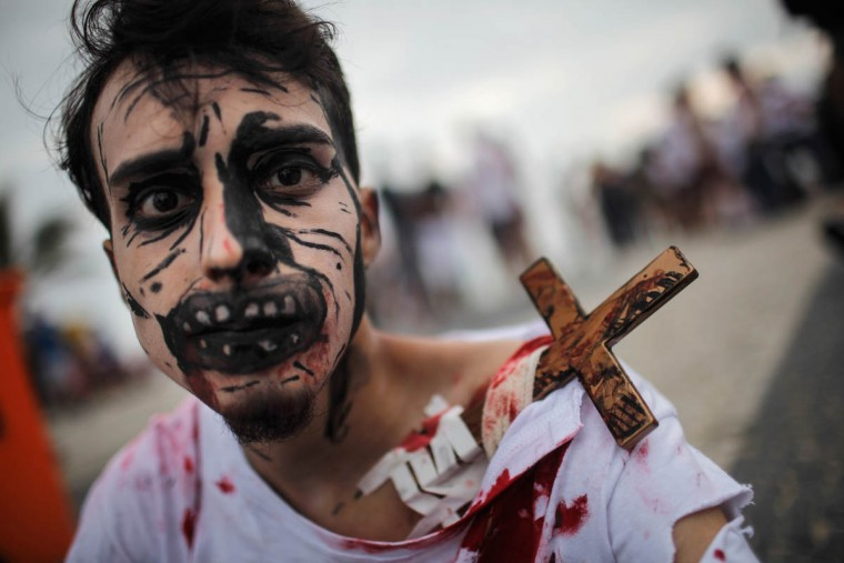 A reveler poses on Ipanema beach during Day of the Dead festivities on November 2, 2015 in Rio de Janeiro, Brazil. Brazilians often mark the traditional Mexican holiday by visiting loved ones' graves and sometimes leaving offerings of food or drink. Many revelers came to Ipanema beach during a 'Zombie Walk'. (Mario Tama/Getty Images)
