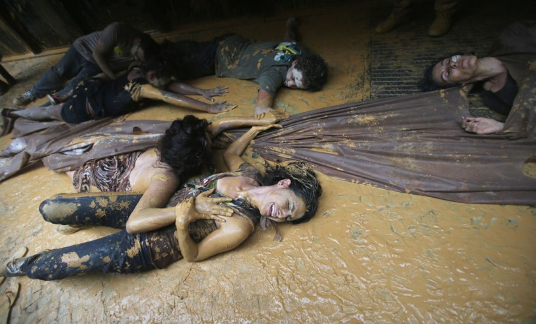 Protesters lay in muddy water, which they splashed at the entrance to Vale headquarters on November 16, 2015 in Rio de Janeiro, Brazil. (Photo by Mario Tama/Getty Images)