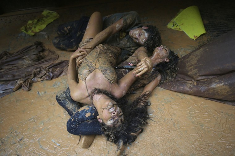 Protesters perform lying in muddy water which they splashed at the entrance to Vale headquarters on November 16, 2015 in Rio de Janeiro, Brazil. The bursting of two dams at the Samarco mining operation, jointly owned by Vale and BHP Billiton, unleashed a flood of muddy waste which mostly leveled a village in Minas Gerais state. The massive mudflow left ten people dead and an environmental aftermath polluting downstream waters. (Photo by Mario Tama/Getty Images)