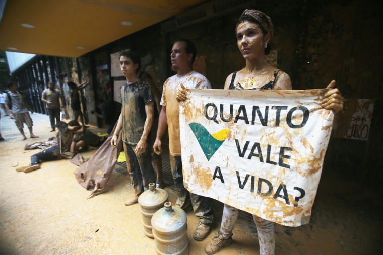Protesters stand amidst muddy water, which they splashed at the entrance to Vale headquarters on November 16, 2015 in Rio de Janeiro, Brazil. The bursting of two dams at the Samarco mining operation, jointly owned by Vale and BHP Billiton, unleashed a flood of muddy waste, which mostly leveled a village in Minas Gerais state. The massive mudflow left ten people dead and an environmental aftermath polluting downstream waters. (Photo by Mario Tama/Getty Images)