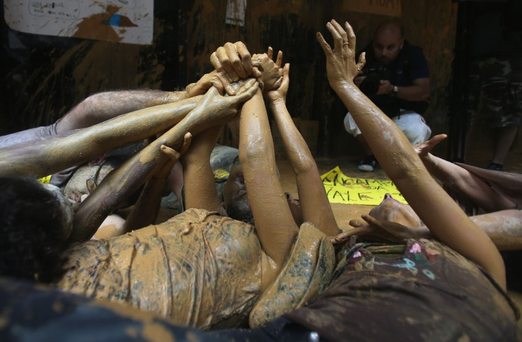 Protesters perform lying in muddy water, which they splashed at the entrance to Vale headquarters on November 16, 2015 in Rio de Janeiro, Brazil. (Photo by Mario Tama/Getty Images)