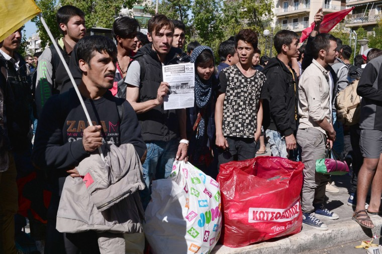 Migrants stand with their belengings, as hundreds of migrants are forced to leave the Victoria Square to be transferred to a former Olympic hall in Athens, on October 1, 2015. Hundreds of mainly Afghan migrants had set up tents on Victoria Square in recent days, prompting protests from the city of Athens and local residents. Greek authorities on Thursday hastily reopened a derelict sports hall from the Athens 2004 Olympics to house hundreds of migrants who were sleeping on the streets of the capital. (Louisa Gouliamaki/AFP/Getty Images)