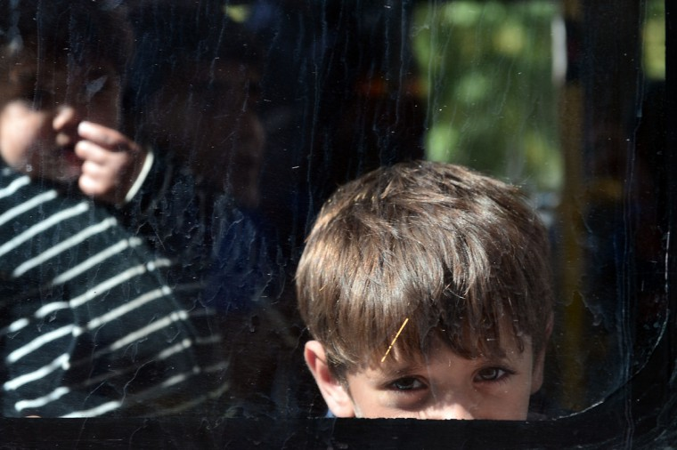 A boy looks out from a bus at the Victoria square in central Athens, as hundreds of migrants board buses to be transferred to a former Olympic hall, on October 1, 2015. Hundreds of mainly Afghan migrants had set up tents on Victoria Square in recent days, prompting protests from the city of Athens and local residents. Greek authorities on October 1, 2015 hastily reopened a derelict sports hall from the Athens 2004 Olympics to house hundreds of migrants who were sleeping on the streets of the capital. (Louisa Gouliamaki/AFP/Getty Images)