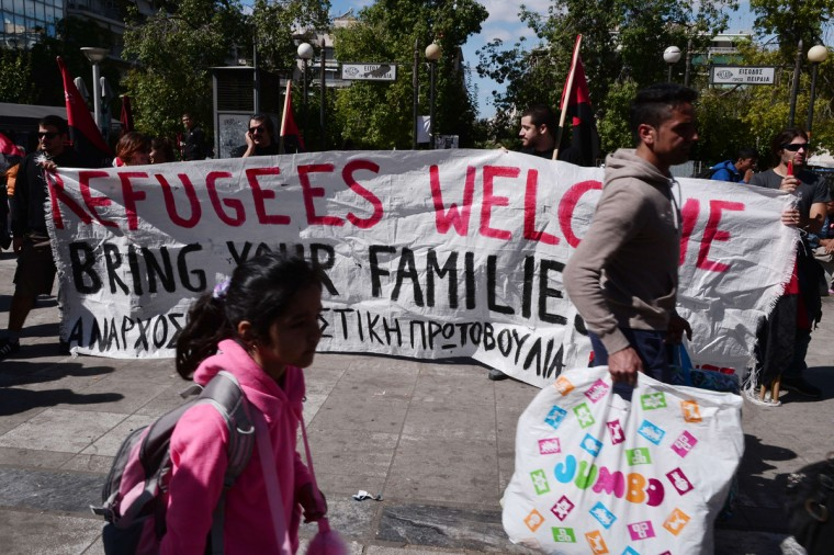 "People, part of a pro-migrant group, hold a banner reading ""Refugees welcome, Bring your families"" at the Victoria square in central Athens, as migrants walk to board buses to be transferred to a former Olympic hall, on October 1, 2015. Hundreds of mainly Afghan migrants had set up tents on Victoria Square in recent days, prompting protests from the city of Athens and local residents. Greek authorities on October 1, 2015 hastily reopened a derelict sports hall from the Athens 2004 Olympics to house hundreds of migrants who were sleeping on the streets of the capital. (Louisa Gouliamaki/AFP/Getty Images)"