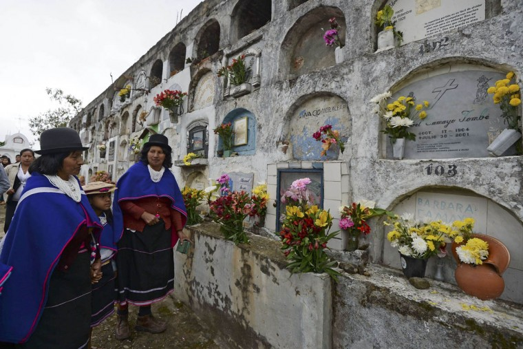 """Colombian indigenous women of the Misak ethnic group visit the tombs of relatives at the cemetery in Silvia, department of Cauca, Colombia, on November 1, 2015, during the celebration of All Saints Day. The Misaks are, of the hundred indigenous groups that inhabit Colombia, the ones who have their customs best preserved, including a colorful ceremony of offerings to the dead, closely related to the cult of """"Mother Earth"""" and the New Year. The Day of the Offerings is celebrated between November 1 and 2, when the favorite food of the dead is prepared to receive their spirits and harmonize the territory. (Luis Robayo/Getty Images)"""