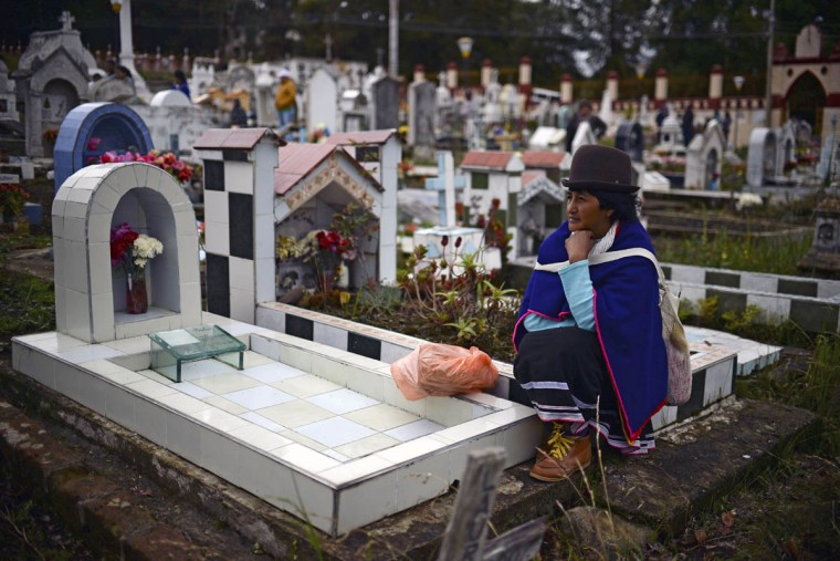"""A Colombian indigenous woman of the Misak ethnic group sits by the grave of a relative at the cemetery in Silvia, department of Cauca, Colombia, on November 1, 2015, during the celebration of All Saints Day. The Misaks are, of the hundred indigenous groups that inhabit Colombia, the ones who have their customs best preserved, including a colorful ceremony of offerings to the dead, closely related to the cult of """"Mother Earth"""" and the New Year. The Day of the Offerings is celebrated between November 1 and 2, when the favorite food of the dead is prepared to receive their spirits and harmonize the territory. (Luis Robayo/Getty Images)"""