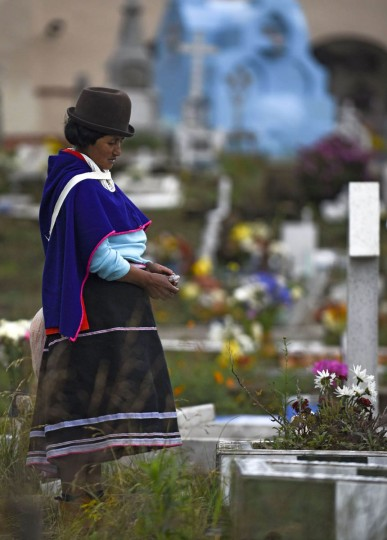 """A Colombian indigenous woman of the Misak ethnic group prays by the grave of a relative at the cemetery in Silvia, department of Cauca, Colombia, on November 1, 2015, during the celebration of All Saints Day. The Misaks are, of the hundred indigenous groups that inhabit Colombia, the ones who have their customs best preserved, including a colorful ceremony of offerings to the dead, closely related to the cult of """"Mother Earth"""" and the New Year. The Day of the Offerings is celebrated between November 1 and 2, when the favorite food of the dead is prepared to receive their spirits and harmonize the territory. (Luis Robayo/Getty Images)"""