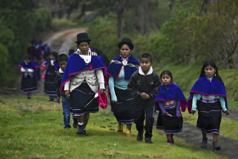 """Colombian indigenous people of the Misak ethnic group walk in Guambia, department of Cauca, Colombia, on November 1, 2015, during the celebration of All Saints Day. The Misaks are, of the hundred indigenous groups that inhabit Colombia, the ones who have their customs best preserved, including a colorful ceremony of offerings to the dead, closely related to the cult of """"Mother Earth"""" and the New Year. The Day of the Offerings is celebrated between November 1 and 2, when the favorite food of the dead is prepared to receive their spirits and harmonize the territory. (Luis Robayo/Getty Images)"""