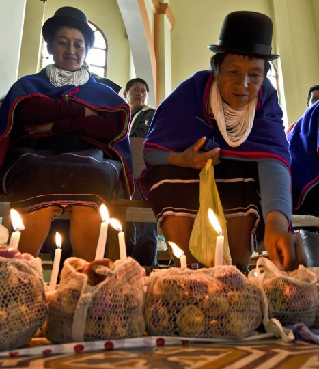 """Colombian indigenous people of the Misak ethnic group take part in an offering ceremony at Our Lady of Chiquinquira church in Silvia, department of Cauca, Colombia, on November 1, 2015, during the celebration of All Saints Day. The Misaks are, of the hundred indigenous groups that inhabit Colombia, the ones who have their customs best preserved, including a colorful ceremony of offerings to the dead, closely related to the cult of """"Mother Earth"""" and the New Year. The Day of the Offerings is celebrated between November 1 and 2, when the favorite food of the dead is prepared to receive their spirits and harmonize the territory. (Luis Robayo/Getty Images)"""