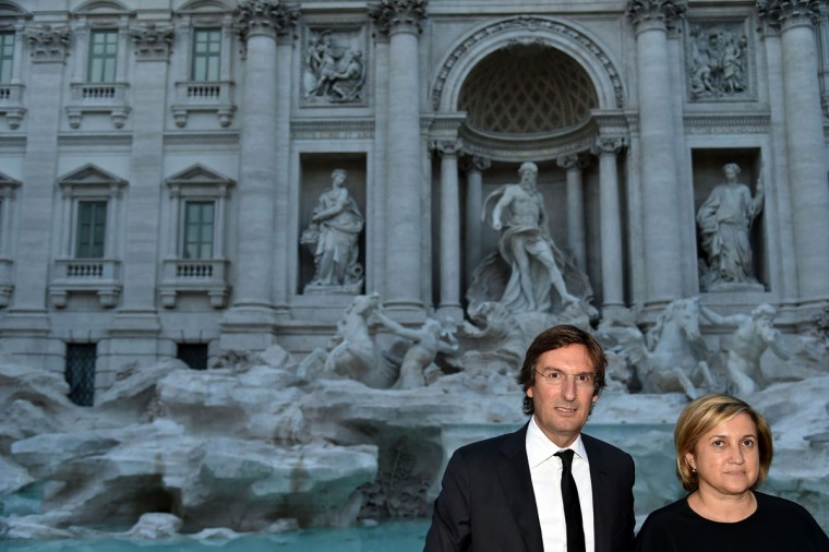 Fendi's Ceo, Pietro Beccari, poses with Silvia Venturini Fendi in front of the restored Trevi fountain prior its inauguration on November 3, 2015 in central Rome. (ALBERTO PIZZOLI/AFP/Getty Images)