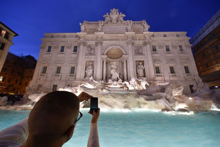 A man takes a picture of the restored Trevi fountain during its inauguration on November 3, 2015 in central Rome. (ALBERTO PIZZOLI/AFP/Getty Images)