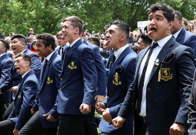 Students perform a Hakka for New Zealand's All Blacks after their arrival at a parade and official welcome for the team in Auckland on November 4, 2015, following the team's Rugby World Cup win against Australia. The New Zealand All Blacks returned to Auckland after they won the Rugby World Cup beating Australia in the final in England. (AFP Photo/Michael Bradley)