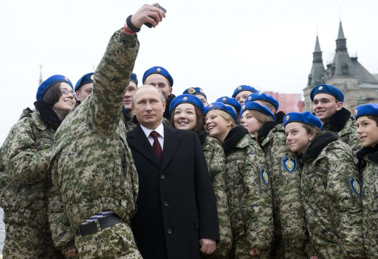 Russian President Vladimir Putin (C) poses for a selfie with young activists at the Red Square in Moscow on November 4, 2015 during celebrations for National Unity Day marking the 403rd anniversary of the 1612 expulsion of Polish occupation forces from the Kremlin. (AFP Photo/Natalia Kolesnikova)